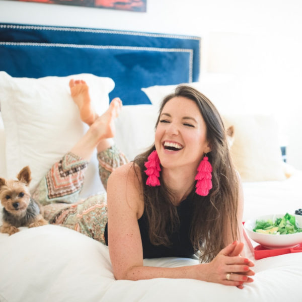 Isabel Smith Nutritionist smiling and laying on the bed with her dog and salad